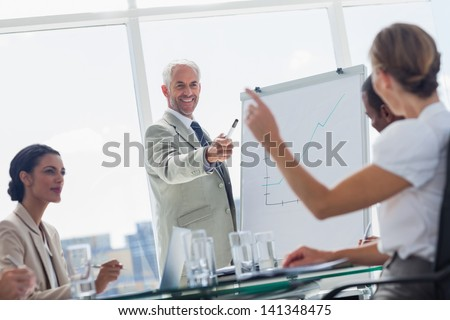 Cheerful boss pointing at a colleague during a meeting - stock photo