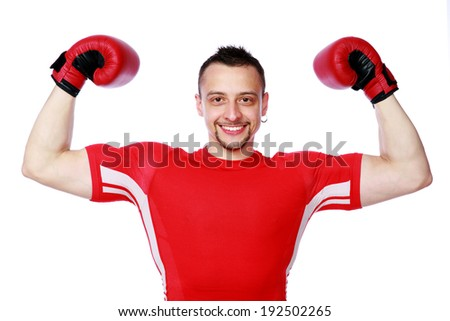 Cheerful boxer man winner raising arms over white background - stock photo