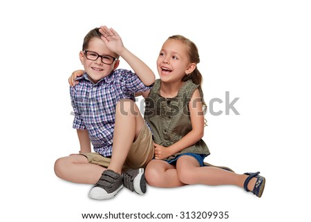 Cheerful boy and a girl are siting together on the white background. - stock photo