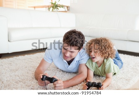 Cheerful boy and his father playing video games while lying on a carpet - stock photo