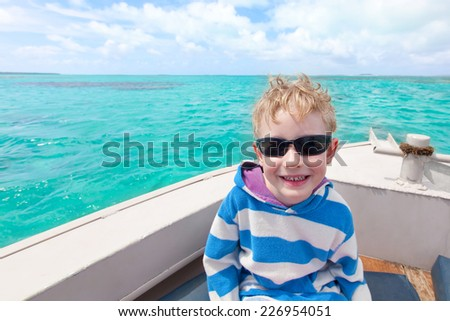 cheerful boy enjoying boat ride during tropical vacation - stock photo