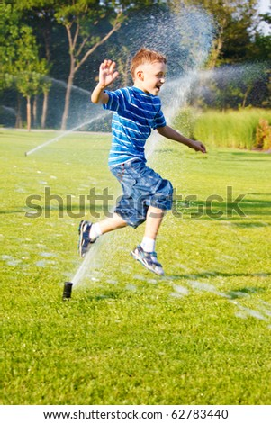 Cheerful boy having fun running from sprinkles - stock photo
