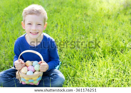cheerful boy holding basket full of colorful easter eggs sitting on the grass in the park after egg hunt