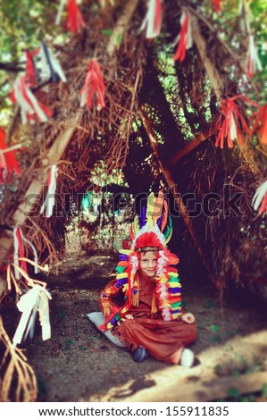 cheerful boy in a bright suit Indian sitting in a tent - stock photo