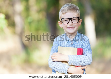 cheerful boy in glasses holding book and ready for school - stock photo