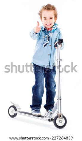 Cheerful boy in jeans, with scooter, showing thumbs up - stock photo