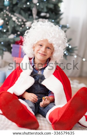 Cheerful boy is sitting near New Year fir-tree. He is wearing white wig and red costume. The kid is smiling and looking at the camera playfully - stock photo