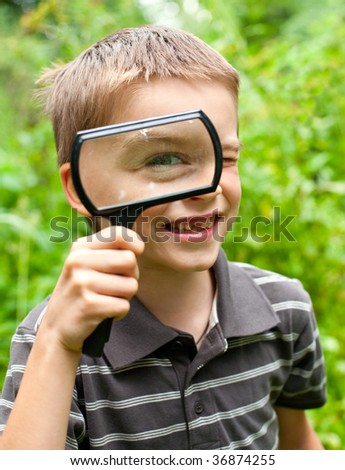 Cheerful boy looking through hand magnifier, shallow DOF