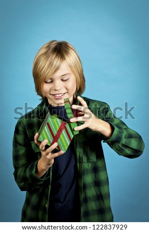Cheerful boy opening his gift box over turquoise background, Model: Josh Chapman - stock photo
