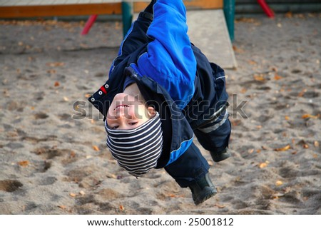 Cheerful boy playing at the playground (winter time)
