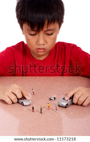 cheerful boy playing model toy cars - stock photo