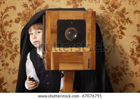 cheerful boy retro photographer with vintage camera over old wallpaper background - stock photo