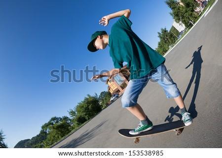 Cheerful boy riding a skateboard on the street. Fish-eye lens. - stock photo