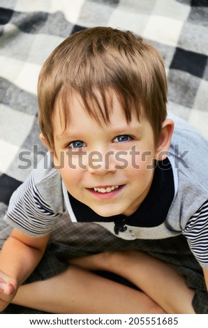 cheerful boy sitting on carpet and looking from the bottom up. horizontal - stock photo