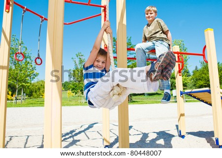 Cheerful boy swinging on rope - stock photo
