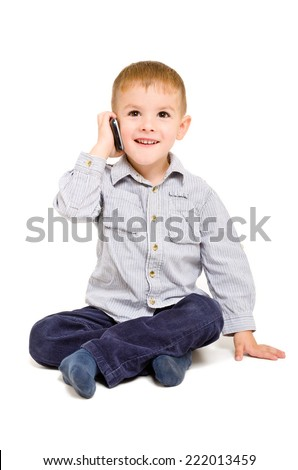 Cheerful boy talking on the phone sitting on the floor isolated on white background - stock photo