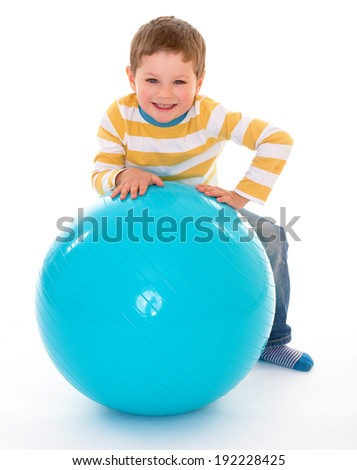 Cheerful boy with a smile relies on the big blue ball, isolated on white background - stock photo