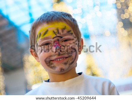 Cheerful boy with makeup on his face, perhaps he tiger - stock photo
