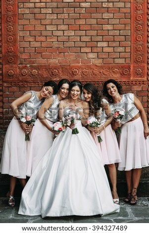 Cheerful bride & bridesmaids with bouquets posing outdoors - stock photo