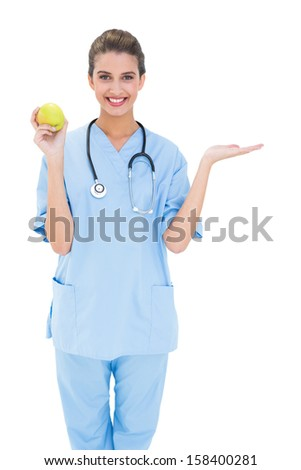 Cheerful brown haired nurse in blue scrubs holding a green apple on white background