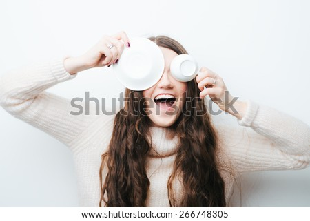 cheerful brunette girl fooling around with a cup on a white background - stock photo