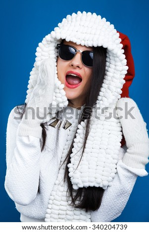 Cheerful brunette girl, wearing in sunglasses, white sweater and gloves, posing like she is screaming with scarf on her head, on the blue background, in studio, waist up - stock photo