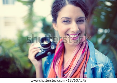 Cheerful brunette photographer standing outside smiling at camera on a sunny day - stock photo