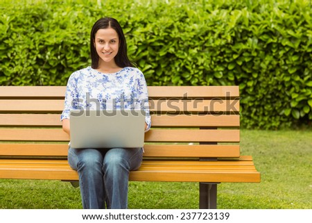 Cheerful brunette sitting on bench using laptop in the park - stock photo