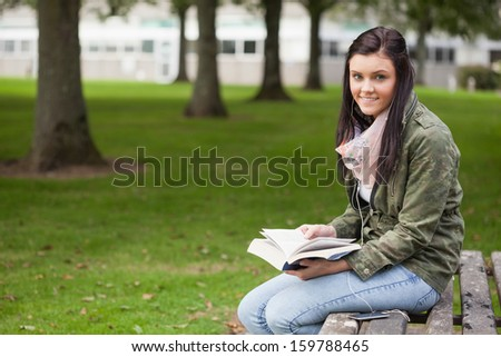 Cheerful brunette student sitting on bench reading on campus at college