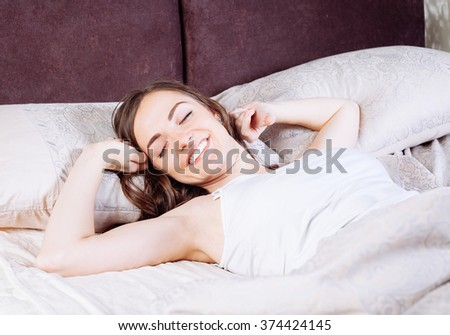 Cheerful brunette  woman awaking on white sheet in her bed at home - stock photo