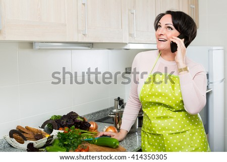 Cheerful brunette woman chatting with somebody on phone as cooking dinner  - stock photo