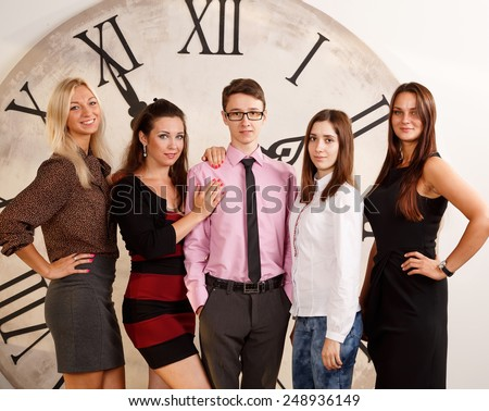 Cheerful business group. Four women and one man were gathered together. Students in practice, working in the office. Group of people of different nationalities on the background of the clock. - stock photo