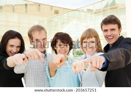 Cheerful business group of executives all pointing at you - stock photo