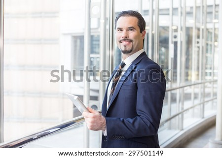 Cheerful business man holding tablet and looking at the camera in modern business building - stock photo