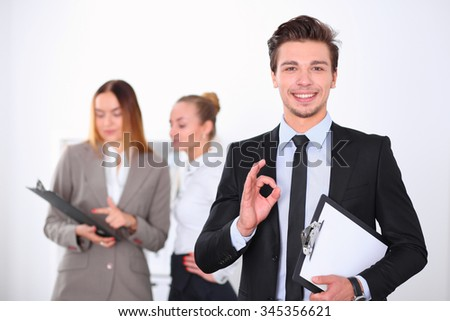 Cheerful business man in office with colleagues in the background, start  up team