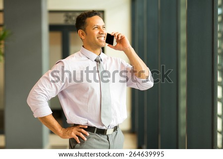 cheerful business man talking on smart phone in office - stock photo