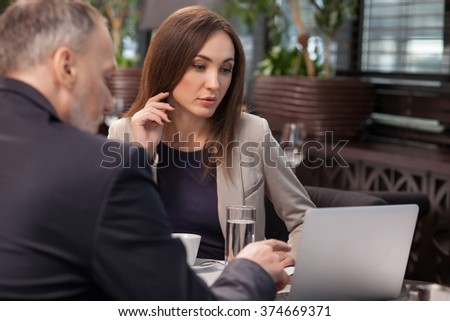 Cheerful business partners are discussing the project in restaurant. The mature man is pointing finger at the laptop and explaining. The woman is looking at the screen with interest - stock photo