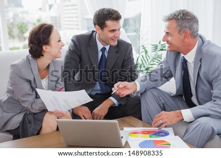 Cheerful business people analyzing financial graphs of their company in cosy meeting room - stock photo