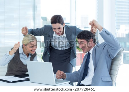 Cheerful business people cheering in front of laptop at office desk - stock photo
