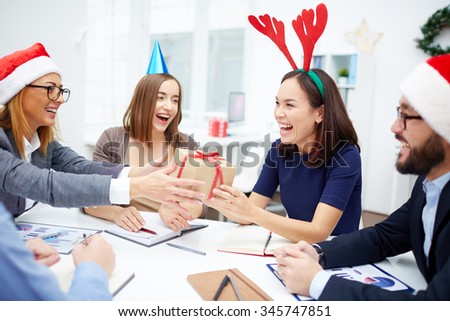 Cheerful business people giving Christmas presents during meeting - stock photo