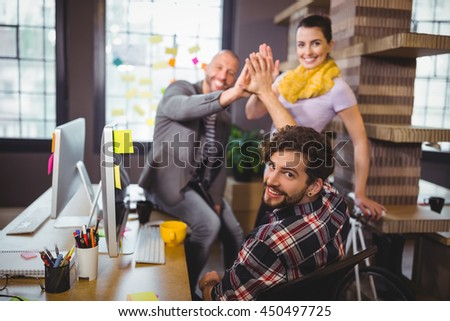 Cheerful business people high fiving in creative office - stock photo