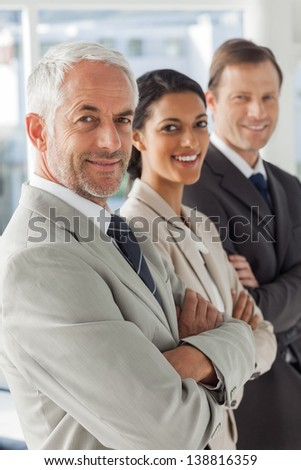 Cheerful business people looking in the same way with their arms crossed - stock photo