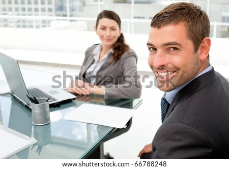 Cheerful business people working on a laptop during a meeting in the office - stock photo