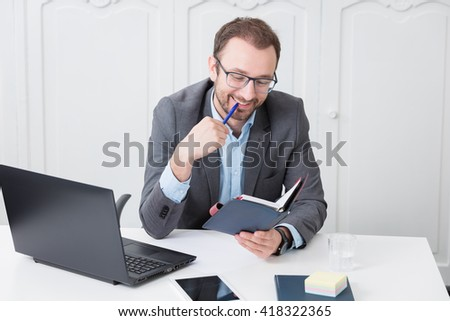Cheerful business professional looking at meeting schedule notebook