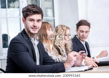 Cheerful business. Smiling businessman sitting at a desk and looking happily at the camera while his colleague businessmen talking in the background - stock photo