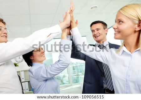 Cheerful business team holding their hands together with enthusiasm - stock photo