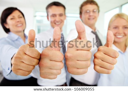 Cheerful business team holding their thumbs up with enthusiasm - stock photo
