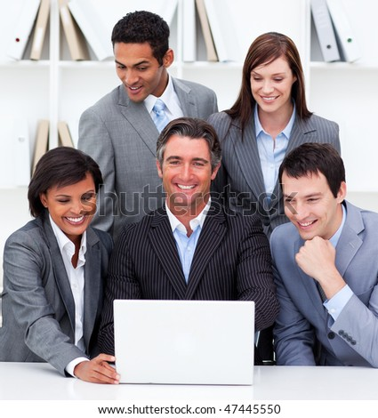 Cheerful business team looking at a laptop in the office