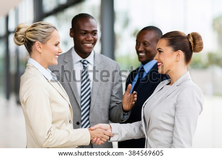 cheerful business team welcoming businesswoman - stock photo