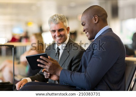 cheerful business travelers using tablet computer at airport - stock photo